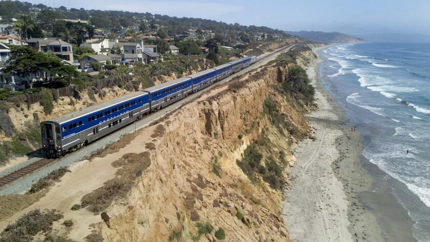 An Amtrak Surfliner train travels along the eroding sandstone cliffs in Del Mar.