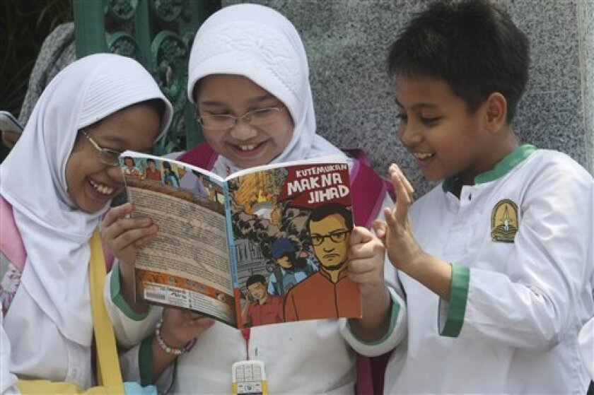 Students read a comic book with an anti-extremist theme at a primary school Friday, Sept. 9, 2011 in Jakarta, Indonesia. The real life adventures of former al-Qaida-linked terrorist Nasir Abas have become a new comic book in Indonesia, chronicling his transformation from militant to invaluable ally in the fight against terrorism. (AP Photo/Tatan Syuflana)