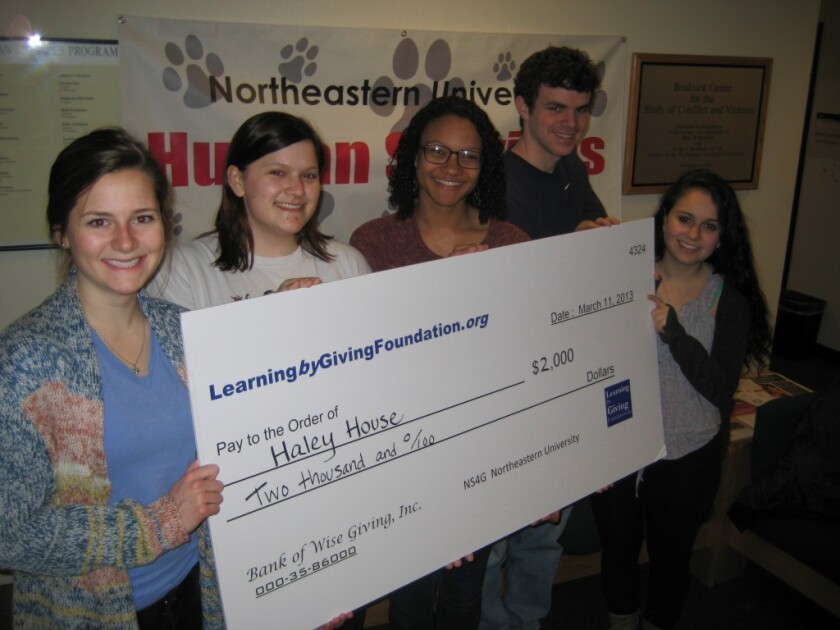 A Warren and Doris Buffett-inspired summer philanthropy course offers no college credit but draws 10,000 students worldwide. Here, Northeastern University Students4Giving program members hold a Learning by Giving Foundation check for Haley House, a Boston-based transitional employment program.