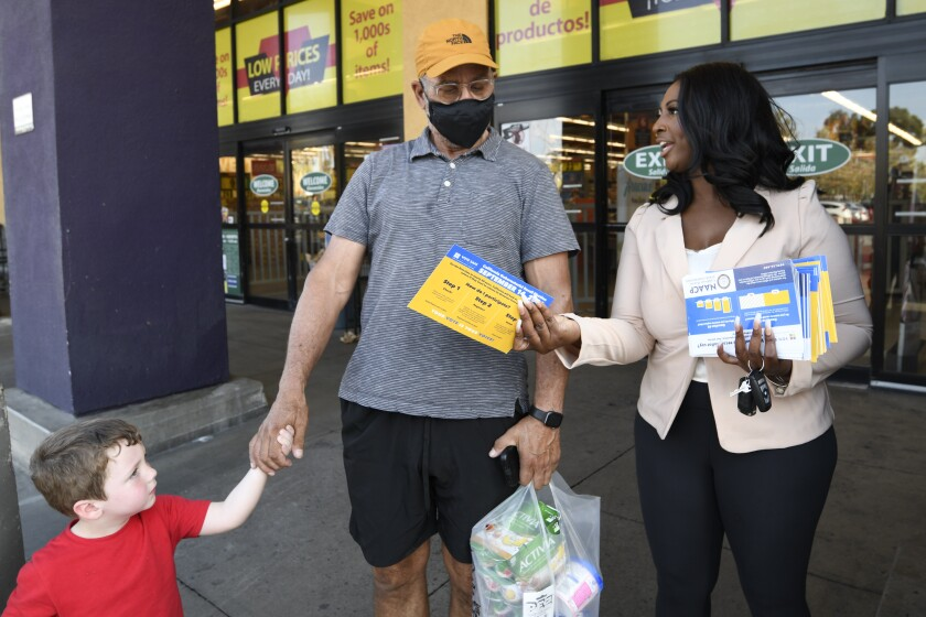 Aeiramique Glass Blake, an NAACP San Diego member, hands out election literature at Jacobs Center in San Diego.
