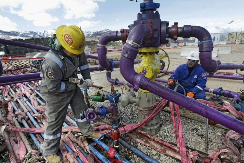 FILE - In this March 29, 2013 file photo, workers tend to a well head during a hydraulic fracturing operation at an Encana Oil & Gas (USA) Inc. gas well outside Rifle, in western Colorado. The vast majority of economists surveyed this month by The Associated Press say lifting restrictions on exports of oil and natural gas would help the economy even if it meant higher fuel prices for consumers. (AP Photo/Brennan Linsley, File)