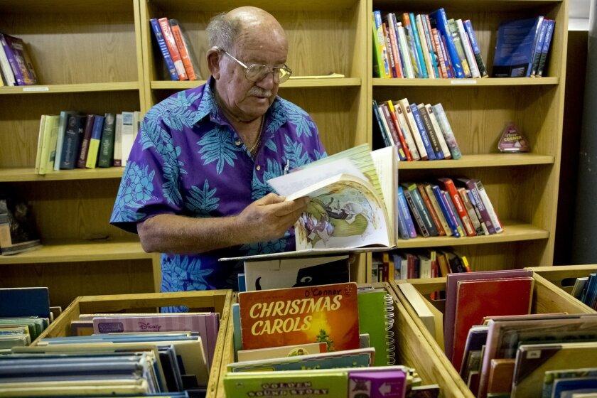 Irwin Herman checks some recently-donated children's books.