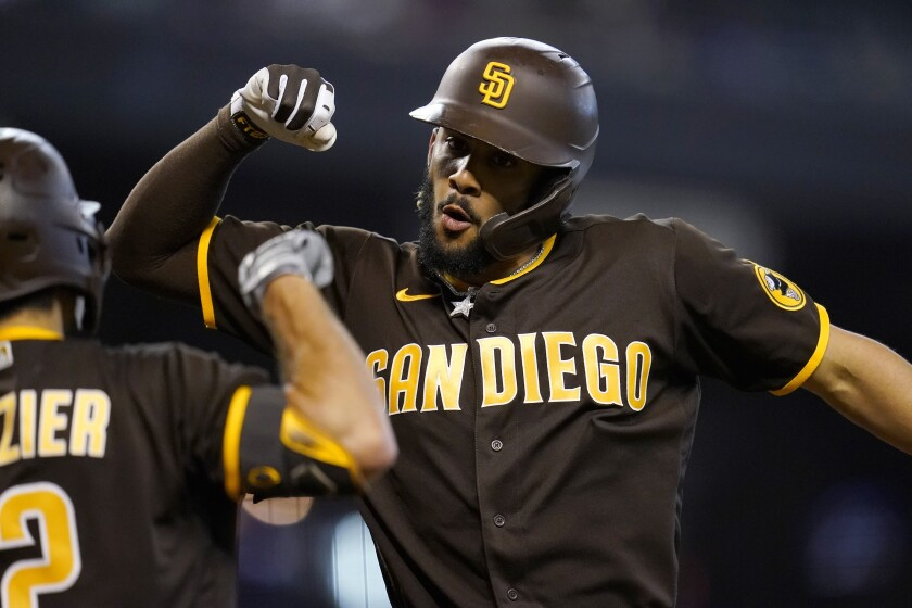 San Diego Padres' Fernando Tatis Jr., right, celebrates his home run against the Arizona Diamondbacks with Padres' Adam Frazier, left, during the fifth inning of a baseball game, Sunday, Aug. 15, 2021, in Phoenix. For Tatis Jr. it was his second home run of the game against the Diamondbacks. (AP Photo/Ross D. Franklin)