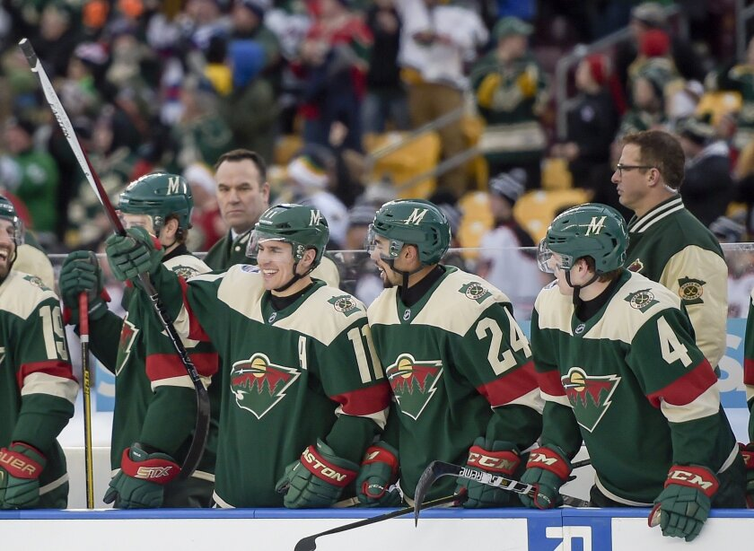 Minnesota Wild left wing Zach Parise, from left, defensiveman Matt Dumba and defensiveman Mike Reilly watch the final seconds of their game as they defeat the Chicago Blackhawks 6-1 during the NHL Stadium Series hockey game, Sunday, Feb. 21, 2016, in Minneapolis. (AP Photo/Craig Lassig)