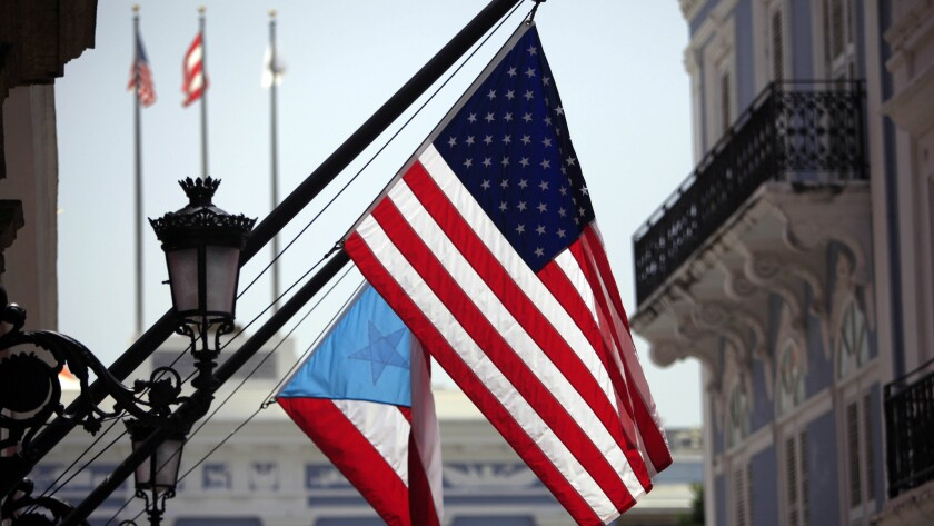 U.S. and Puerto Rico flags hang outside the governor's mansion in Old San Juan, Puerto Rico, on June 29, 2015.
