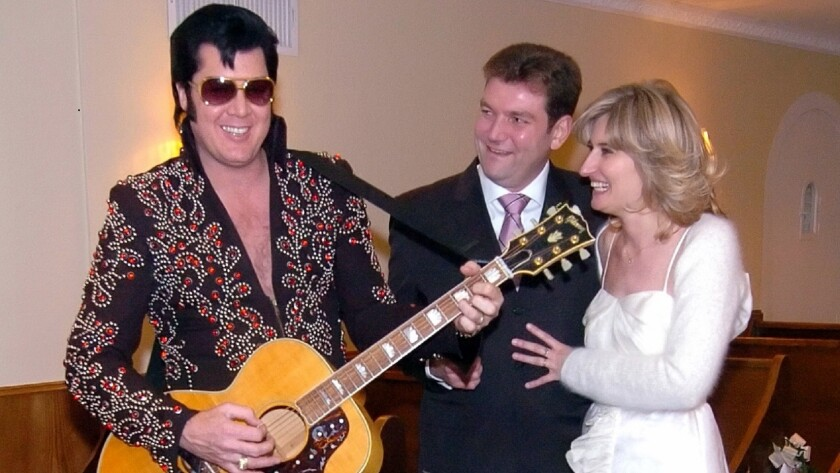 A couple from Belgium enjoy a serenade by an Elvis impersonator during their 2007 wedding at the Viva Las Vegas wedding chapel.