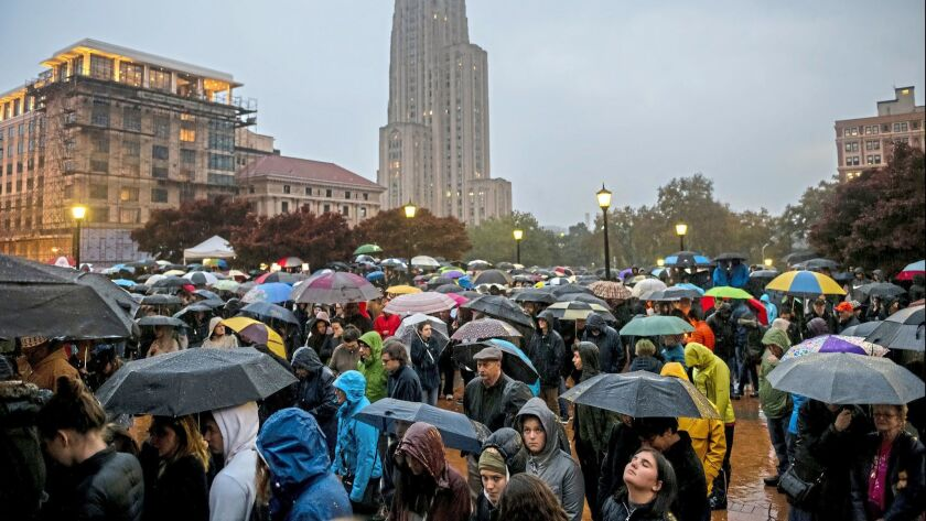 Mourners, most of whom stood in the rain because of over crowdedness, attend a vigil for the victims