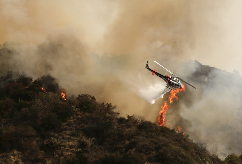 A helicopter drops water on the Colby fire above Azusa. The blaze has charred more than 1,900 acres.
