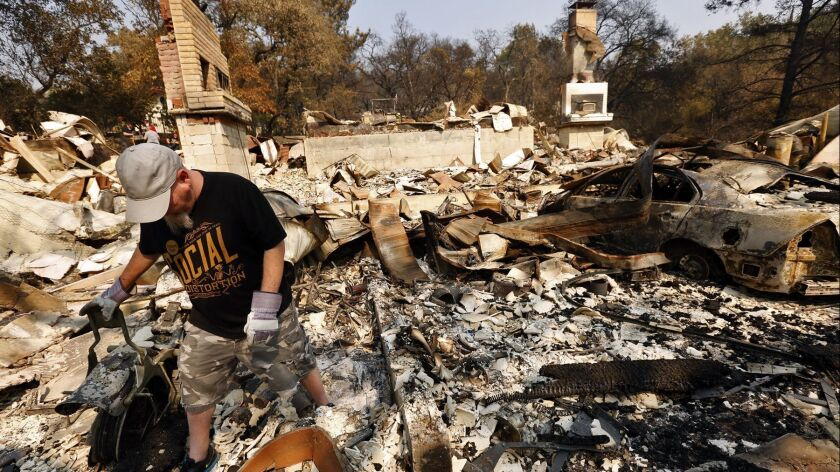 Phil Nelsen walks through the rubble of his grandfather's home that was destroyed in the Atlas fire in Napa on Oct. 13.