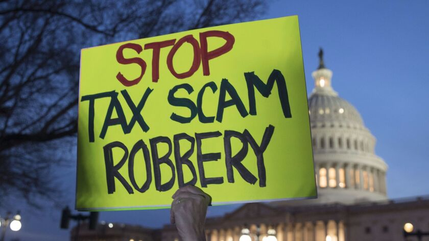 A rally participant holds a sign protesting a Republican-crafted tax cut plan outside the U.S. Capitol Building.