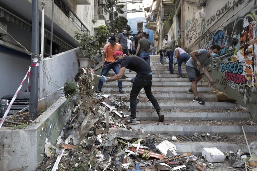 Personas remueven escombros de una calle tras la explosión en Beirut, Líbano, miércoles 5 de agosto de 2020. (AP Foto/Hassan Ammar)