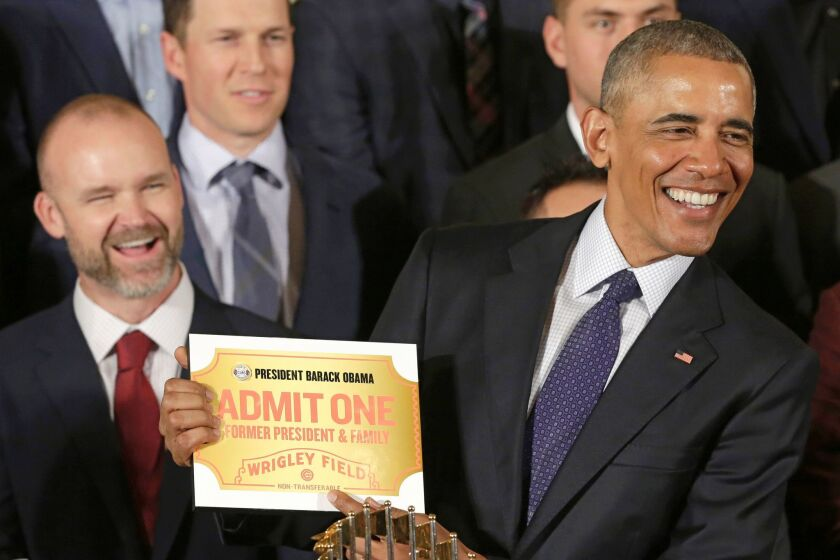 President Obama holds a lifetime admission certificate to Wrigley Field at a White House event honoring the World Series champion Chicago Cubs.