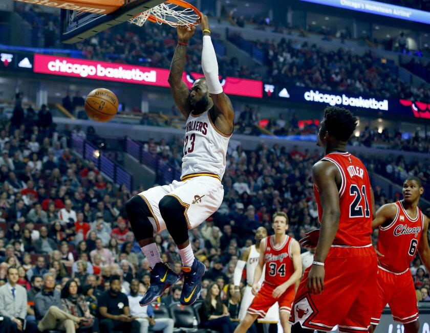 Cleveland Cavaliers forward LeBron James (23) hangs from the rim after dunking against the Chicago Bulls during the first half of an NBA basketball game in Chicago on Saturday, April 9, 2016. (AP Photo/Jeff Haynes)
