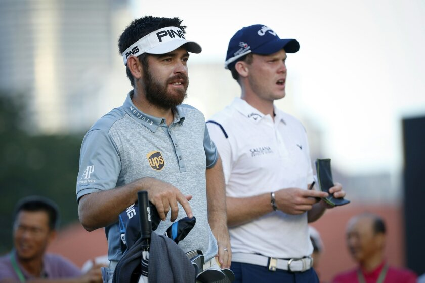 Danny Willet of Britain, right, talks to Louis Oosthuizen of South Africa during day two of the Maybank Championship golf tournament in Kuala Lumpur, Malaysia, Friday, Feb. 19, 2016. (AP Photo/Vincent Thian)