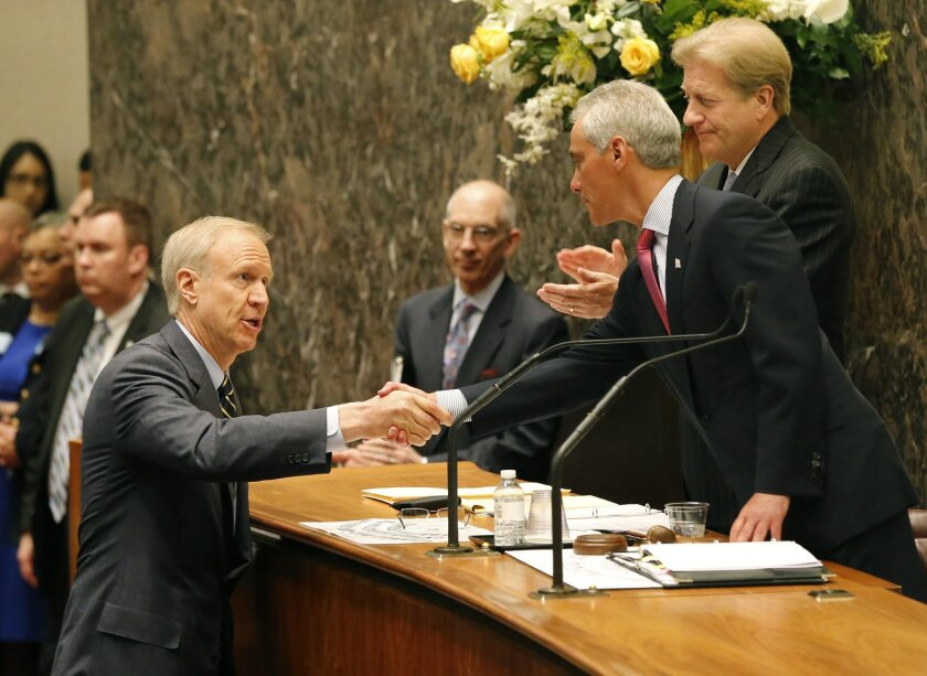 Illinois Gov. Bruce Rauner, left, shakes the hand of Chicago Mayor Rahm Emanuel, right, before Rauner's address to the city council Wednesday, May 6, 2015, in Chicago. The historic address, the first by a sitting governor in the council's chambers, focused on the city's and state's financial and ec