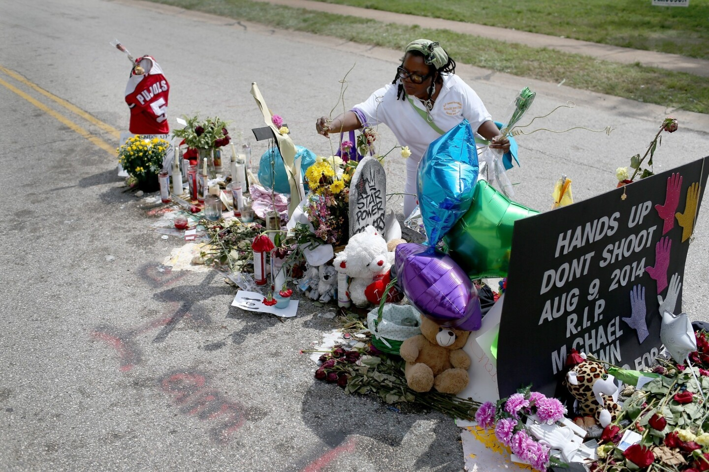Beverly Scott of Chicago adds to the makeshift memorial in Ferguson, Mo., for Michael Brown.