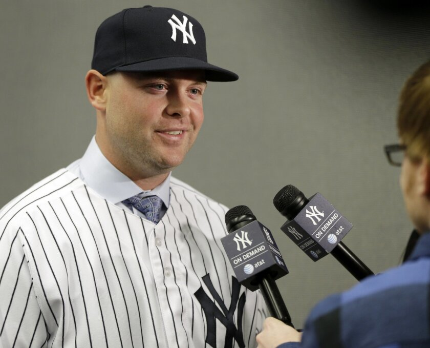 """New York Yankees' Brian McCann is interviewed after a baseball news conference at Yankee Stadium in New York, Thursday, Dec. 5, 2013. McCann, an all-Star catcher, completed his $85 million, five-year contract with the team on Tuesday, in what the team called a """"significant improvement to a key position."""" (AP Photo/Seth Wenig)"""