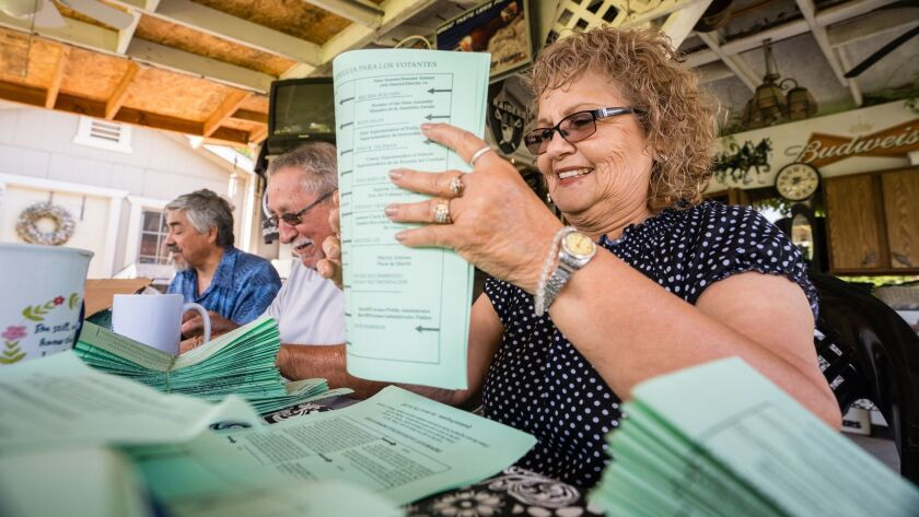 From left, Jose Ojeda, Raul Gomez and Mary Gonzales-Gomez of the Latino Community Roundtable fold Democratic voter guides for distribution in Corcoran, Calif.