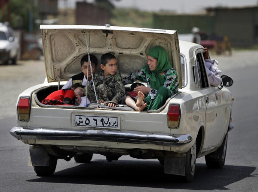 Afghan children ride in the trunk of a car on the outskirts of the capital, Kabul.
