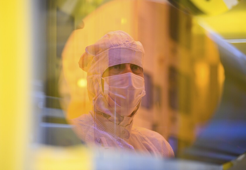 An associate is reflected in a 300-millimeter wafer in the clean room during a press tour of the new semiconductor factory of the Bosch company in Dresden, Germany, May 31, 2021. The chip factory will officially start working on June 7, 2021. (Robert Michael/dpa via AP)
