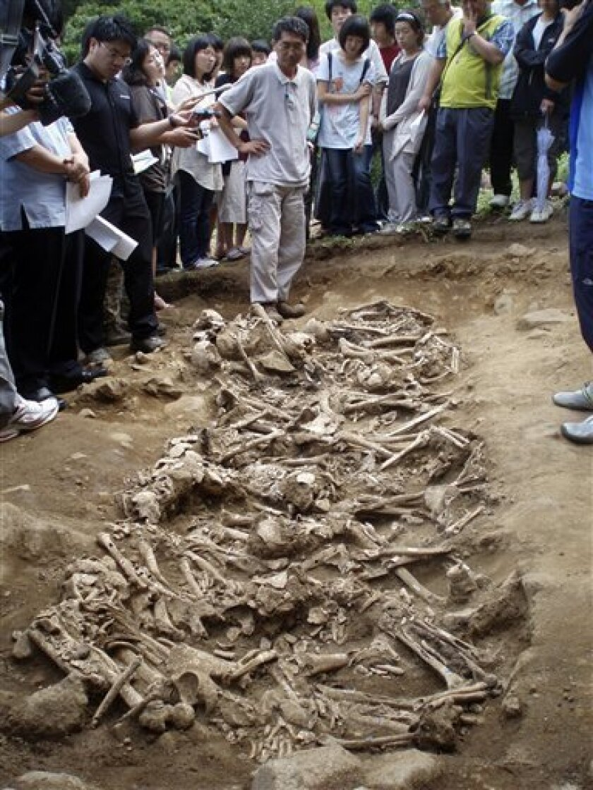 This undated photo released by the Truth and Reconciliation Commission, Republic of Korea shows excavation team members, journalists and family survivors viewing skulls and other human bones at a site in Oegongri, 170 miles southeast of Seoul, South Korea, where the government Truth and Reconciliation Commission exhumed the remains of some 500 civilians believed to have been killed by South Korean troops in early 1951. The commission estimates at least 100,000 supposed leftist sympathizers were summarily executed by their own government in the Korean War's first months. From July to November, crews excavated five of an estimated 150 or more such grave sites. The commission thus far has confirmed two dozen mass executions. (AP Photo/Truth and Reconciliation Commission, Republic of Korea) NO IONLN **