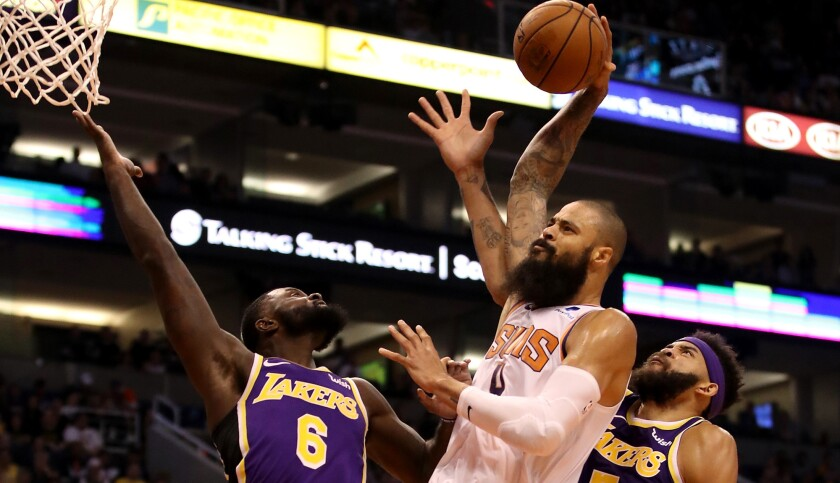 Tyson Chandler tries to dunk against the Lakers' Lance Stephenson (6) and JaVale McGee while playing for the Suns earlier this season.