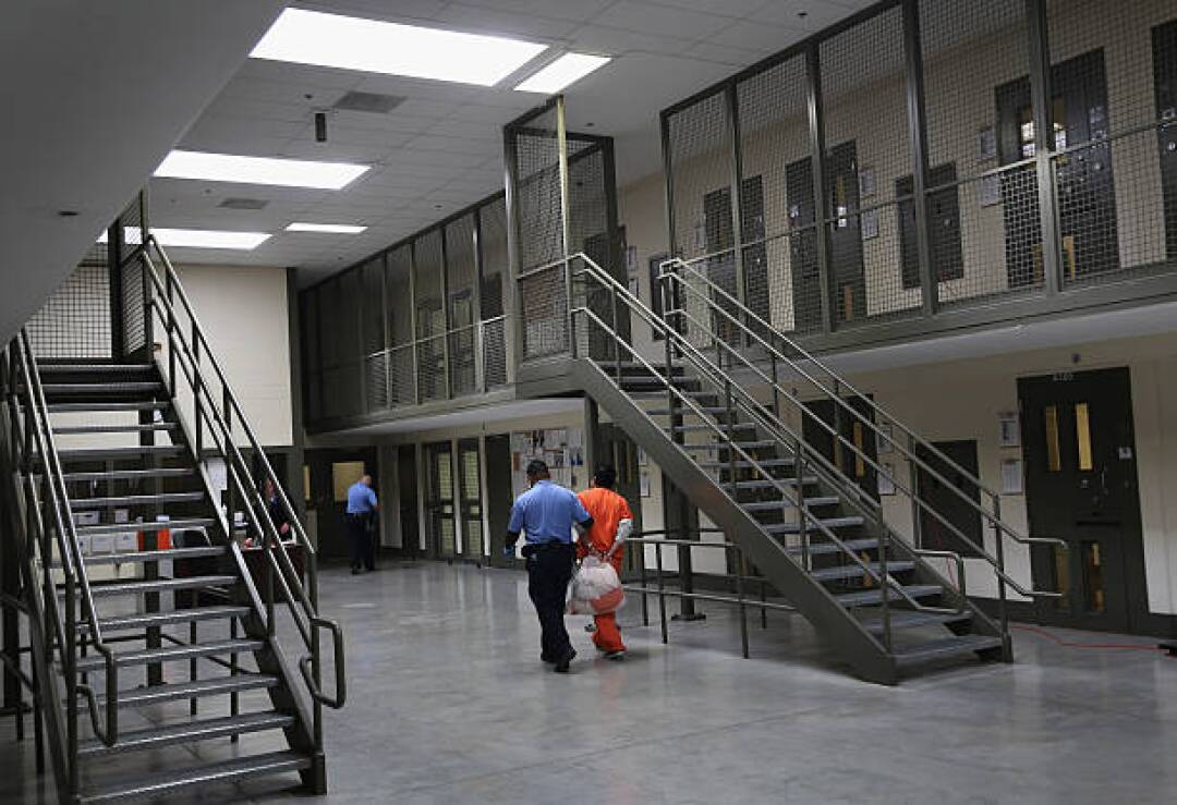 A guard in uniform, left, walks with an immigrant detainee in an orange suit