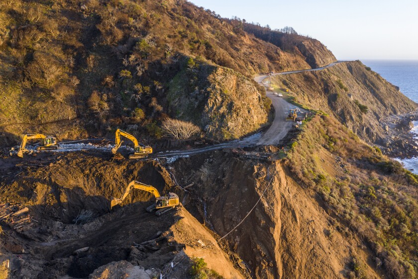 Crews dig debris from a washed-out section of Highway 1 on Feb. 10, 2021.