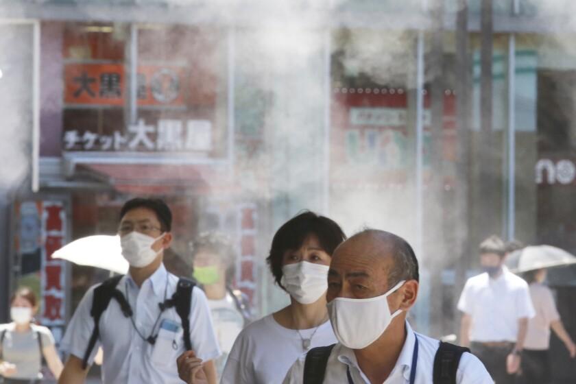 Masked pedestrians walk outside in Tokyo.