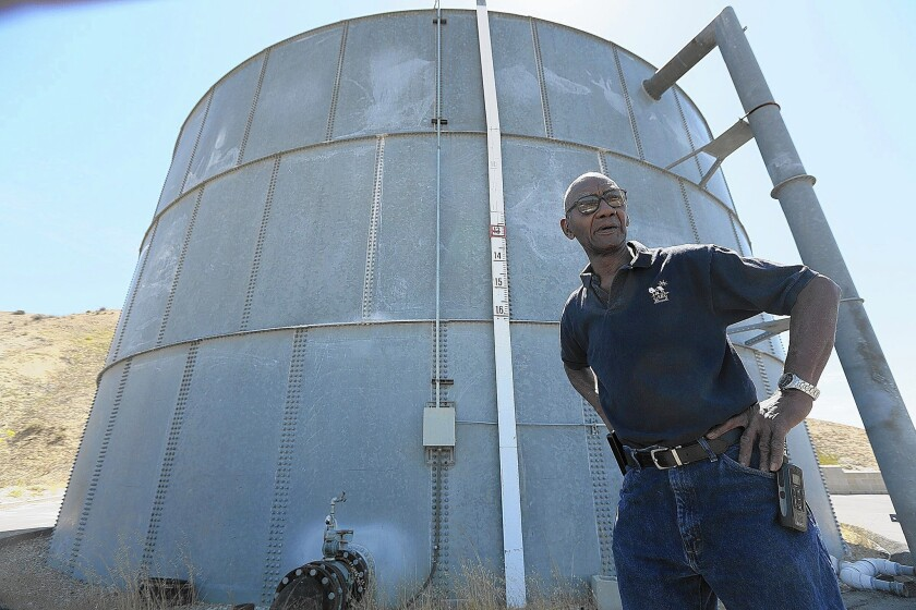 Charles Sturkey, director of operations at LARC Ranch, stands next to a 300,000-gallon tank used to supply water. There are several options for providing water, but they cost more than the facility can afford or are tied up in red tape.