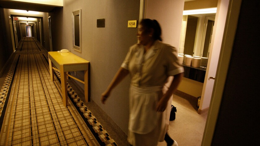 Maria Jimenez, a housekeeper, closes a door on the 12th floor of the Wilshire Grand Hotel in downtown Los Angeles in 2011. A survey commissioned by the travel site Expedia finds that Americans are split on tipping hotel staff.