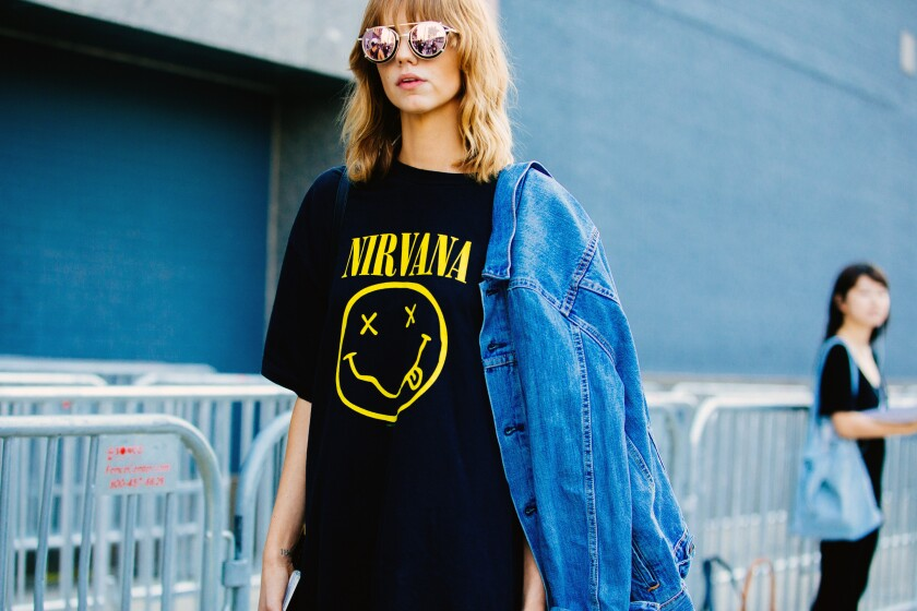 A woman wears a T-shirt with Nirvana's smiley-face logo on it