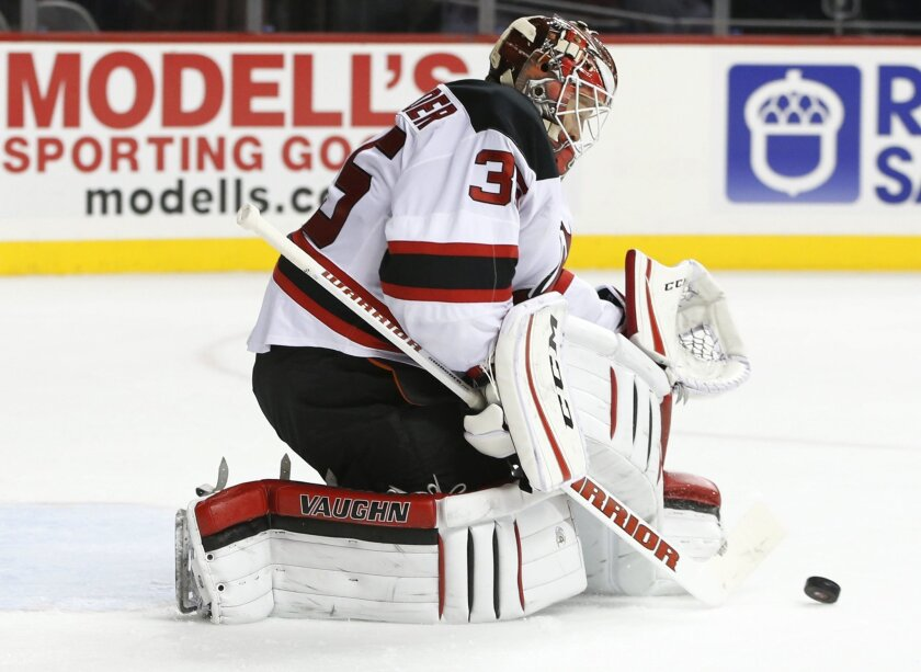New Jersey Devils goalie Cory Schneider makes a save in the second period of an NHL hockey game against the New York Islanders in New York on Tuesday, Nov. 3, 2015. (AP Photo/Kathy Willens)