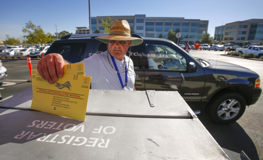 Election worker deposits mail-in ballots.