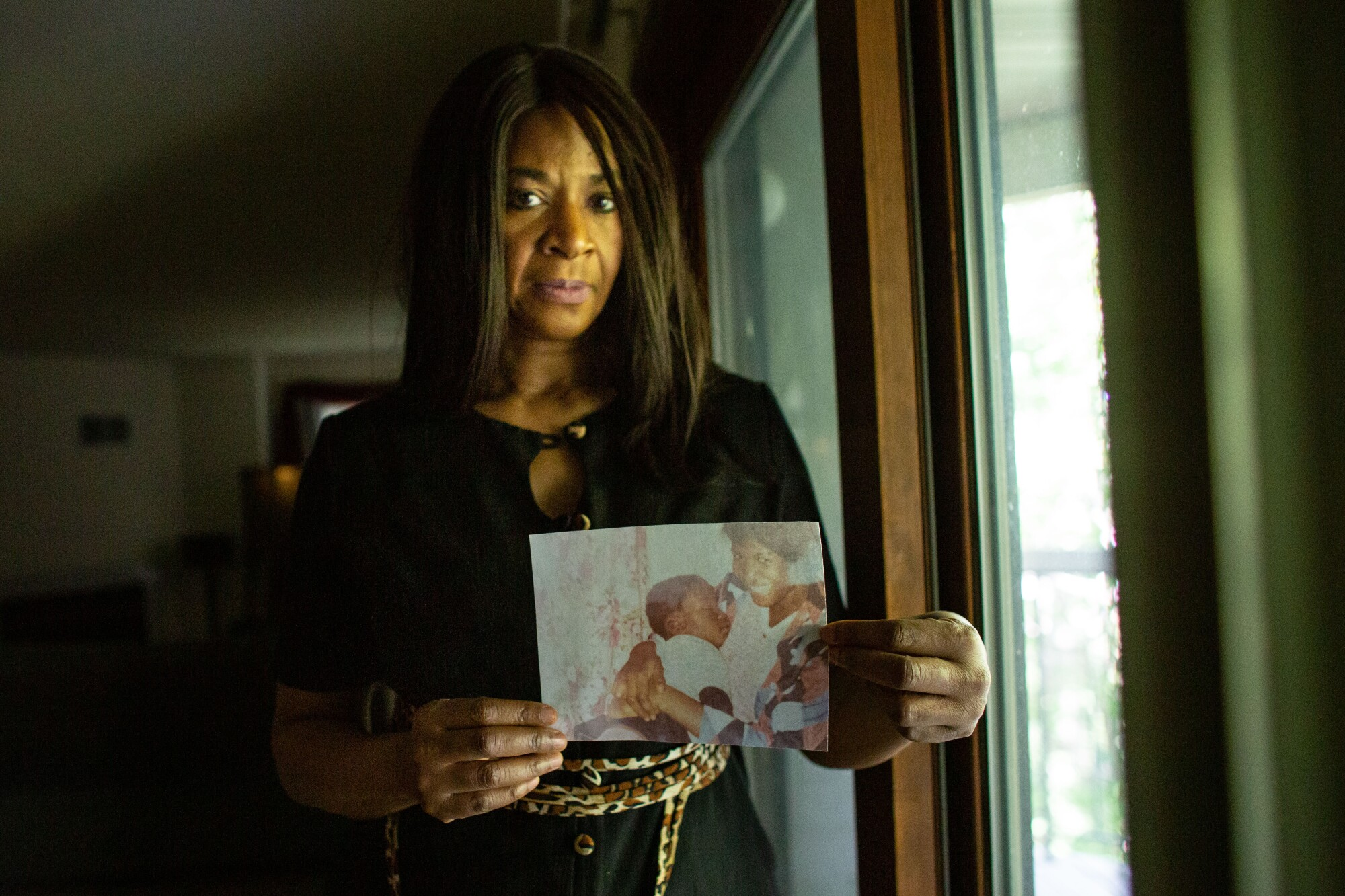 Angela Harrelson of Eagan, Minn., holds a photo George Floyd as a baby.