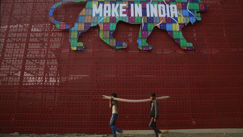 Laborers carry wood piles for preparations of the Make In India summit in Mumbai, India, Tuesday, Fe