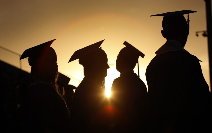 Graduates in caps and gowns gather at sunset