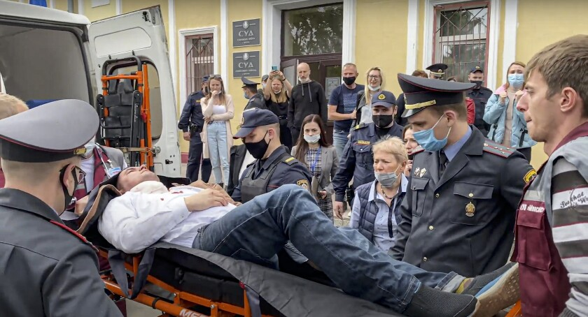 In this handout frame released by Radio Free Europe/Radio Liberty, police officers and paramedics carry Stsiapan Latypau, a Belarusian activist who was attempted to kill himself during a court hearing to protest political repression into an ambulance in Minsk, Belarus, Tuesday, June 1, 2021. Stsiapan Latypau stabbed himself in the neck with a pen while sitting in a cage during the court hearings Tuesday, according to the Viasna human rights center. He has been hospitalized and put in artificial coma after the incident. (Radio Free Europe/Radio Liberty via AP)