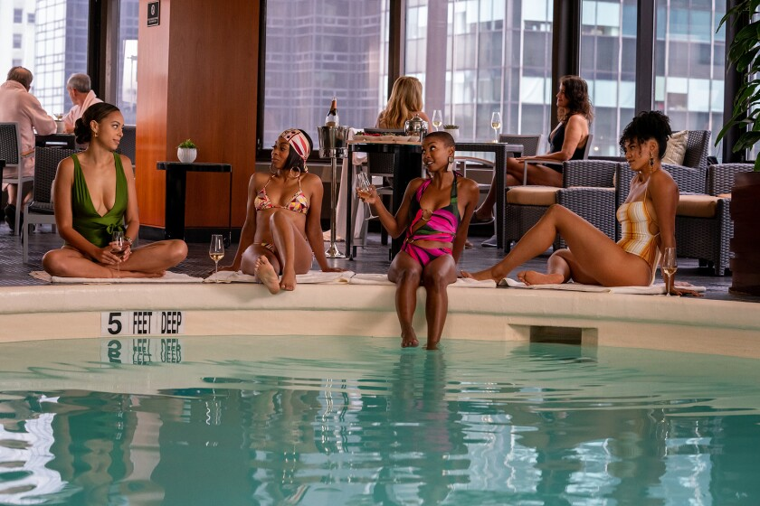 Four women sit at an indoor pool with glasses of wine.
