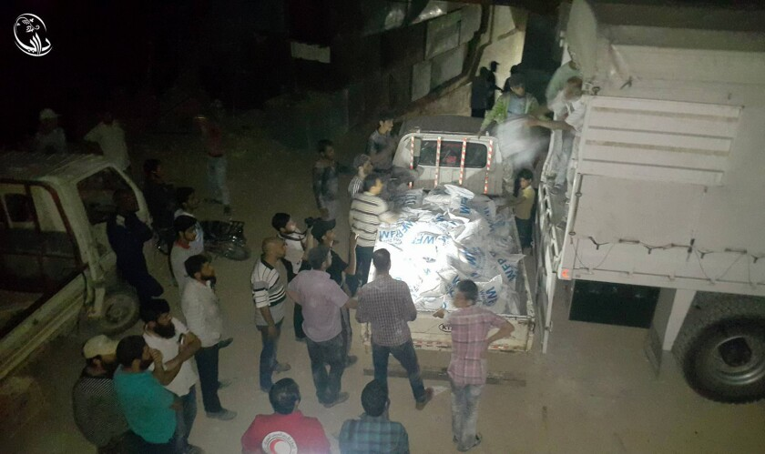 Syrian citizens unload food and other supplies from a truck that entered the besieged town of Daraya.