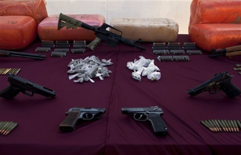 """Weapons and drugs are displayed during a presentation for the media in Tijuana, Mexico, Wednesday, Jan. 5, 2011. According to the army, weapons and drugs were seized and Jesus Israel de la Cruz, aka """"el Tomate"""", an alleged member of the Sinaloa drug cartel, was detained during a conjoined operation with police in Tijuana on Tuesday. (AP Photo/Guillermo Arias)"""