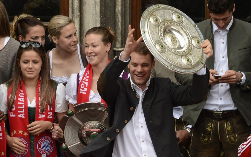 Bayern Munich's goalkeeper Manuel Neuer lifts the Bundesliga trophy on the balcony of the city hall of Munich, southern Germany, Sunday, May 24, 2015, as the team of FC Bayern Munich celebrate their soccer championships victory. At left members of the women's team of Bayern Munich who won the Ladies' championships. (AP Photo/Philipp Guelland)