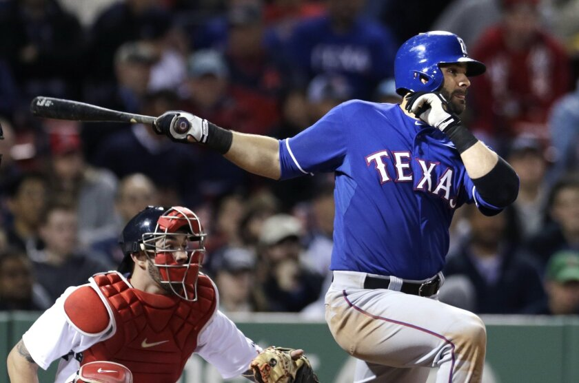 Texas Rangers' Mitch Moreland follows through on a single during the ninth inning of a baseball game against the Boston Red Sox at Fenway Park in Boston, Thursday, May 21, 2015. (AP Photo/Charles Krupa)