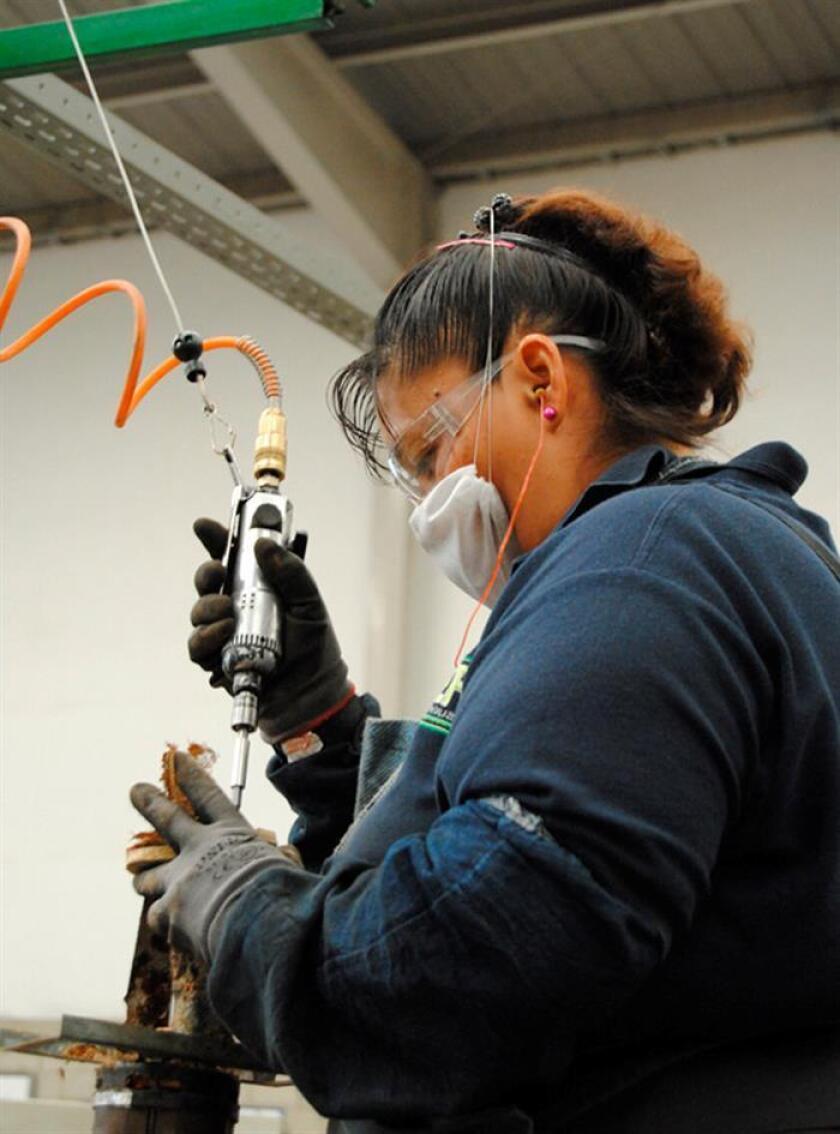 Fotografía cedida por la empresa Recicla Electrónicos México (REMSA), fechada el 11 de enero de 2018, que muestra a una mujer desarmando un aparato electrónico, en Ciudad de México, (México). EFE/REMSA/SOLO USO EDITORIAL