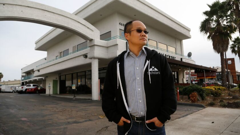 Ping Wang stands near the business building where his family once owned bakery as well as a landlord to other businesses that operated from their building.