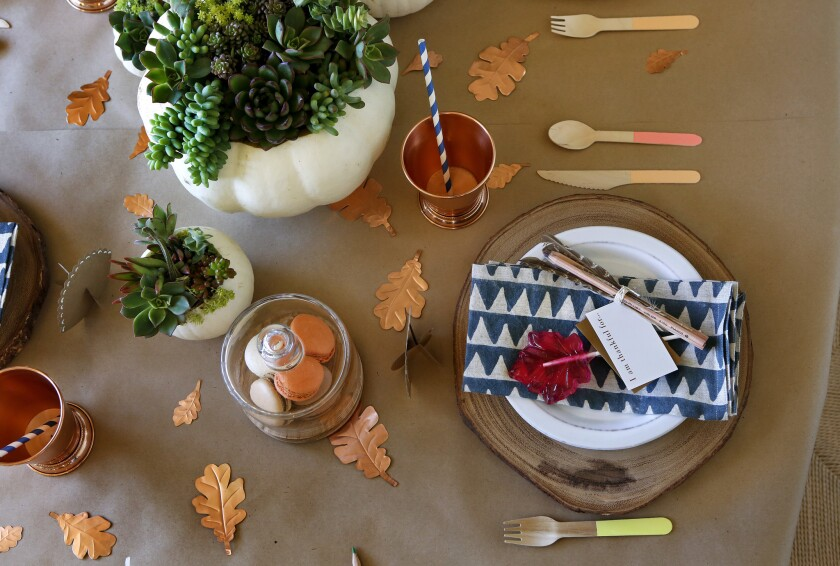 Wooden, disposable utensils, copper leaves, and a lollipop on the place setting are part of a kid's tablescape for the holidays, arranged by Shannon Wollack, David Ko, and Julianne Goldmark, designers with Studio Life.Style.