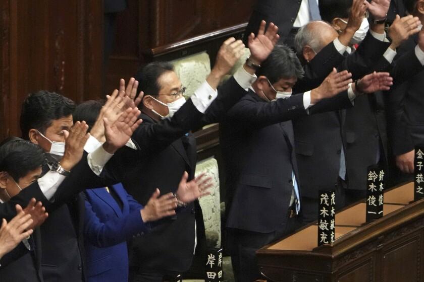 El primer ministro de Japón, Fumio Kishida (centro), y otros legisladores dan tres vivas tras disolver la cámara baja, la más poderosa de las dos del parlamento, durante una sesión extraordinaria, en Tokio, el 14 de octubre de 2021. (AP Foto/Eugene Hoshiko)