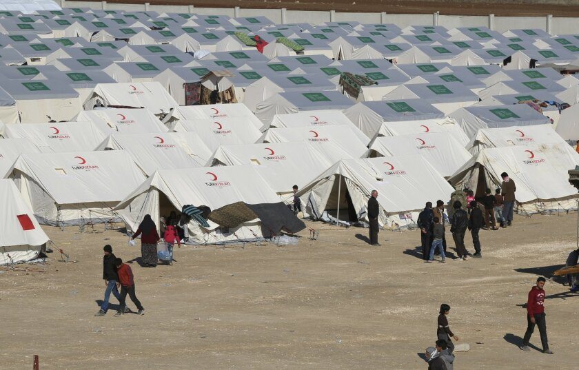 In this photo provided by Turkish Islamic aid group IHH, displaced Syrians walk among a temporary refugee camp in northern Syria, near Bab al-Salameh border crossing with Turkey, Monday, Feb. 8, 2016. Turkey was under pressure from the EU to open its border to up to 35,000 Syrians who have massed a