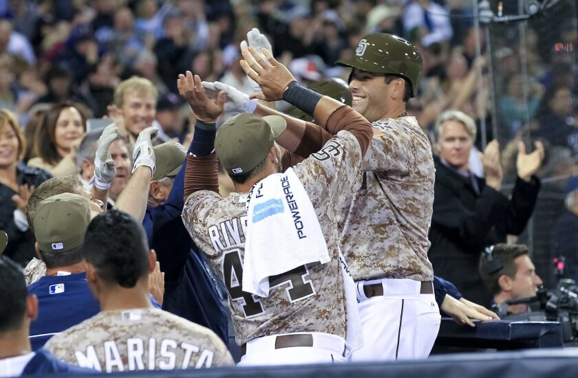 Seth Smith is greeted at the dugout after his game-tying home run against the Los Angeles Dodgers in the eighth inning.