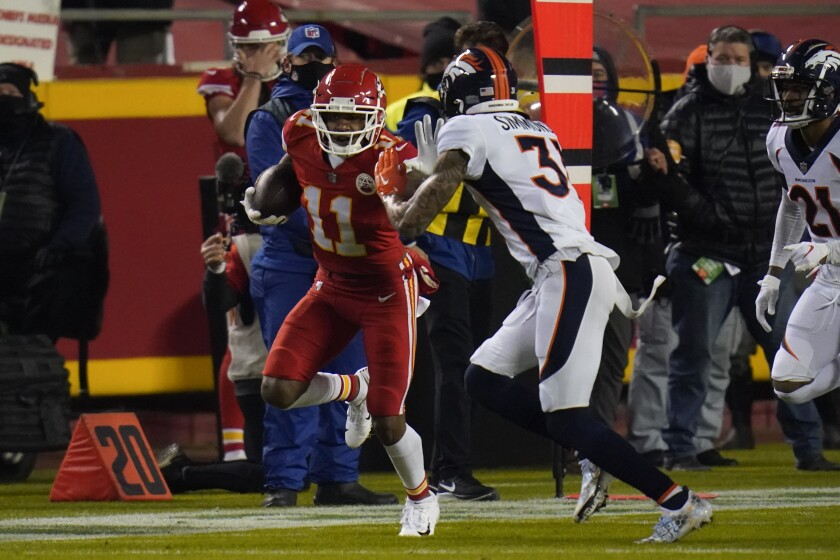 Kansas City Chiefs wide receiver Demarcus Robinson (11) runs after a catch as Denver Broncos free safety Justin Simmons (31) defends in the first half of an NFL football game in Kansas City, Mo., Sunday, Dec. 6, 2020. (AP Photo/Jeff Roberson)